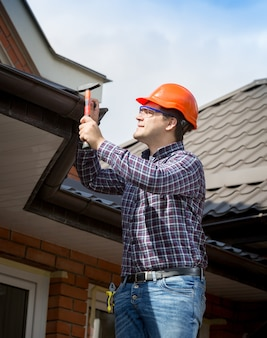 Portrait of young handyman repairing house roof with nails and hammer