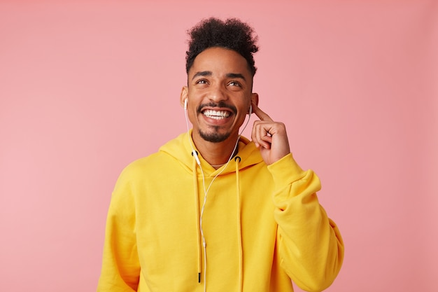 Portrait of young happy african american guy in yellow hoodie, enjoying of his favorite cool song on headphones, dreamly looking up, standing and broadly smiling.