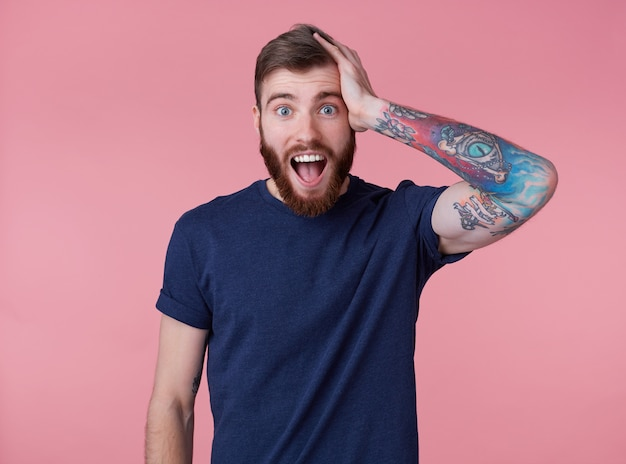 Portrait of young happy amazed attractive red-bearded young guy , wearing a blue t-shirt, with wide open mouth in surprise, hold on to head, heard very good news, isolated over pink background.