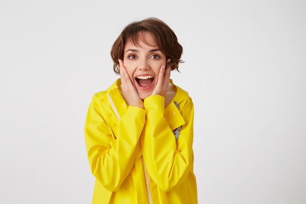 Portrait of young happy amazed cute short haired girl wears in yellow rain coat, with wide open mouth and eyes, touches cheeks, stands over white wall.