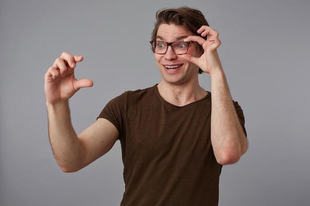 Ritratto di giovane uomo stupito felice con gli occhiali, si erge su sfondo grigio guarda attraverso gli occhiali, mostra le dita qualcosa di minuscolo.