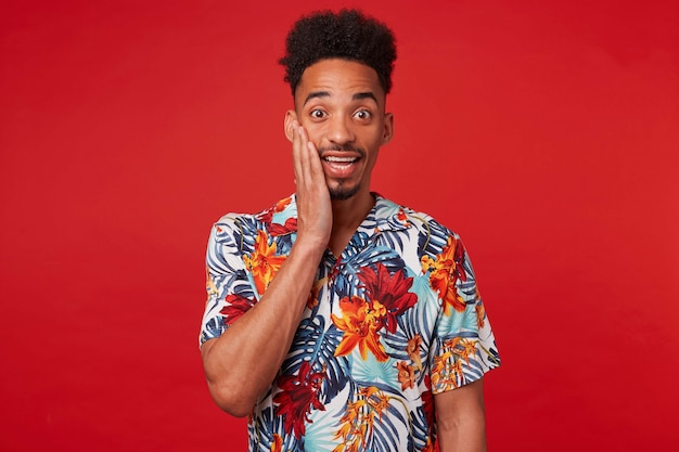 Portrait of young happy amazwed african american guy, wears in hawaiian shirt, looks at the camera with surprised expression touches cheek, stands over red background.