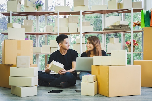 Portrait of young happy asian business couple  using smartphone and laptop for receive order