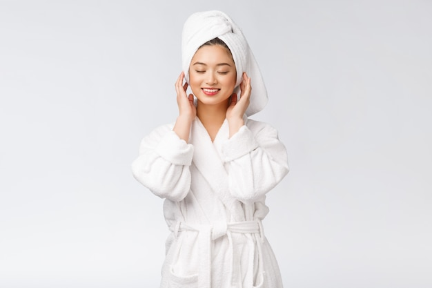 Portrait of a young happy asian lady in bathrobe.isolated in white background.
