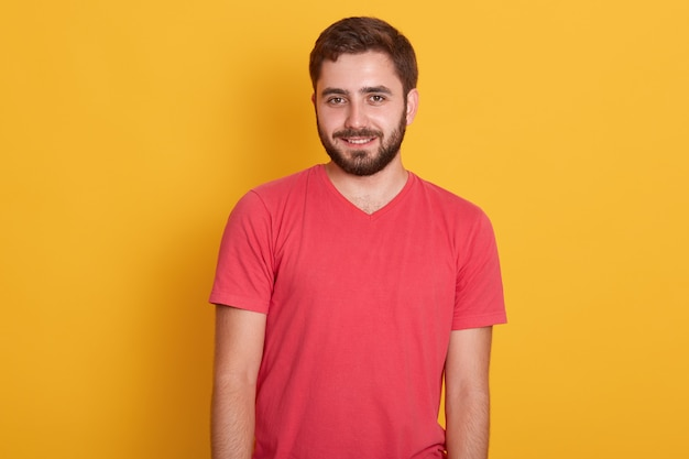 Portrait of young happy attractive bearded guy, handsome male wearing red casual t shirt, smiling