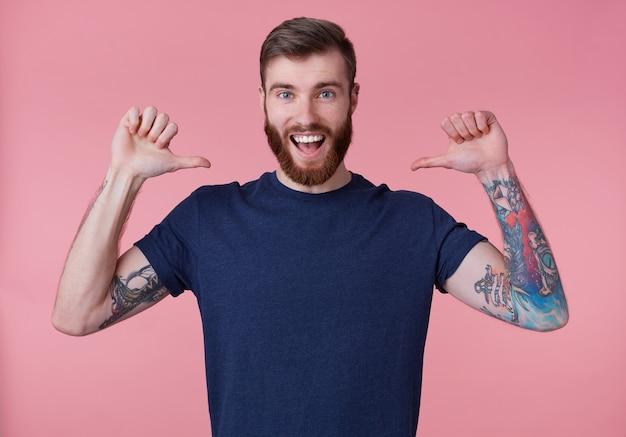 Il ritratto di giovane ragazzo giovane dalla barba rossa attraente felice, indossa una maglietta blu, ampiamente sorridente, si diverte, con le braccia alzate e puntando le dita su se stesso isolato su sfondo rosa.