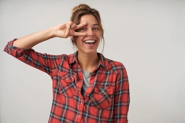 Ritratto di giovane donna bruna felice mantenendo il gesto di pace vicino al suo viso mentre guarda con gioia la fotocamera, in piedi su sfondo bianco in abbigliamento casual