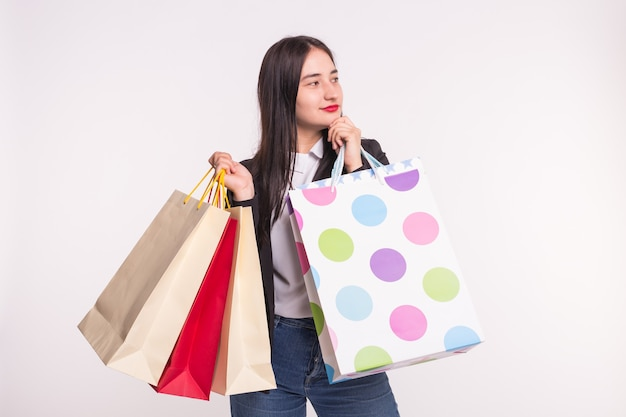 Portrait of young happy brunette woman with shopping bags on white wall