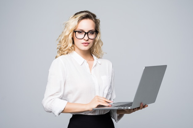 Portrait of a young happy business woman with a laptop over white wall