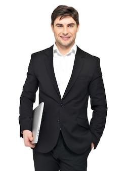 Il ritratto di giovane uomo d'affari felice tiene il computer portatile isolato su bianco.