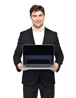 Il ritratto di giovane uomo d'affari felice tiene il computer portatile con lo schermo nero in bianco isolato su bianco.