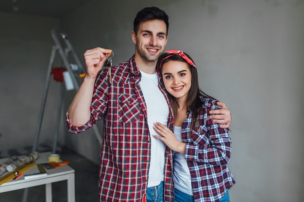 Portrait of young happy casual couple, holding a key, bought new apartment