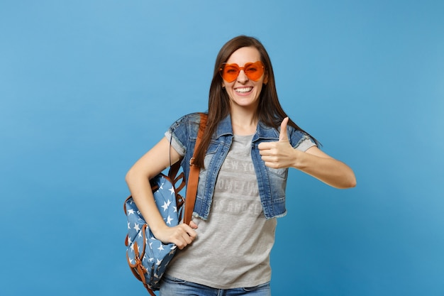 Portrait of young happy cheerful beautiful woman student with backpack in orange heart glasses showing thumb up isolated on blue background. education in high school. copy space for advertisement.