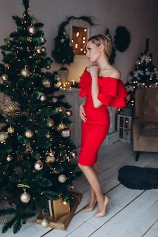 Portrait of young happy cheerful woman in red dress near eve in christmas decorated home. christmas, happiness,beauty, presents concept