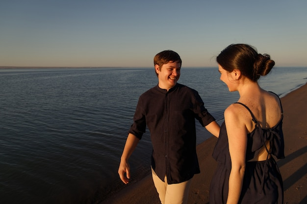 Portrait of a young happy couple in love on the background of the sea in the sunset lighting.