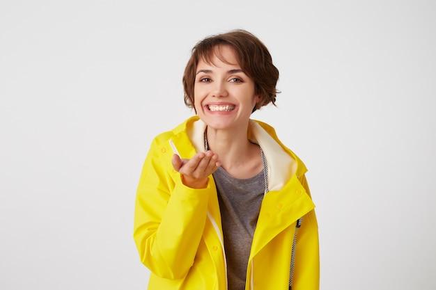 Il ritratto di giovane ragazza dai capelli corti carina felice indossa un impermeabile giallo, sorride ampiamente e punta i palmi verso la telecamera, come tenere qualcosa di piccolo nel palmo, si trova sopra il muro bianco.