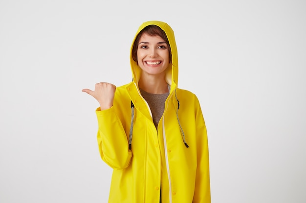 Portrait of young happy cute short haired girl wears in yellow rain coat, broadly smiles, wants to draw you attention and points to copy space at the left, stands over white wall.