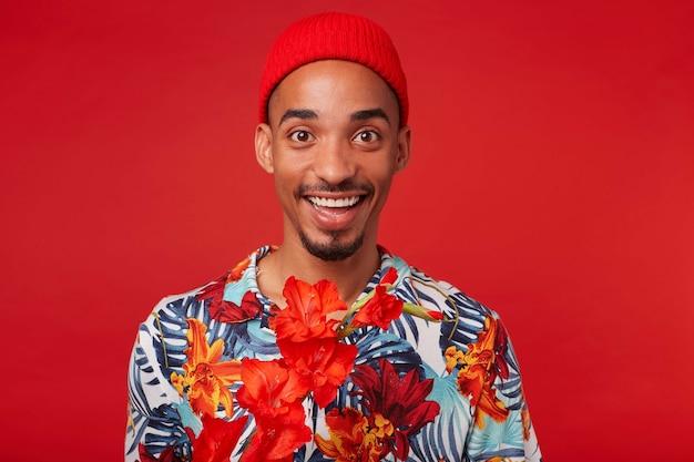 Ritratto di giovane ragazzo dalla pelle scura felice, indossa in camicia hawaiana e cappello rosso, guarda la telecamera con espressione felice, si erge su sfondo rosso.