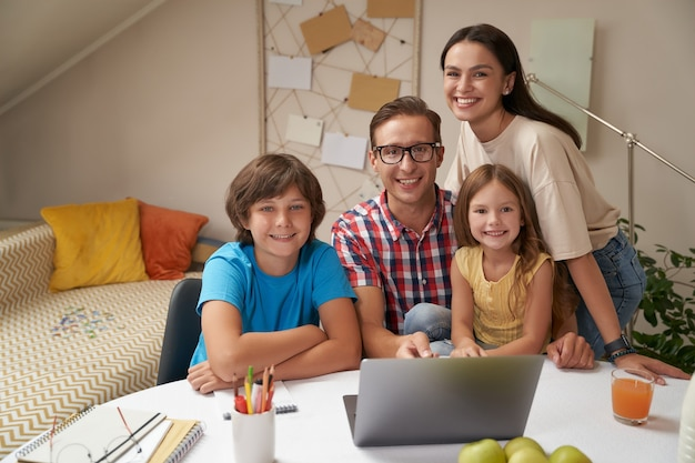 Portrait of young happy family looking at camera and smiling while doing homework together or