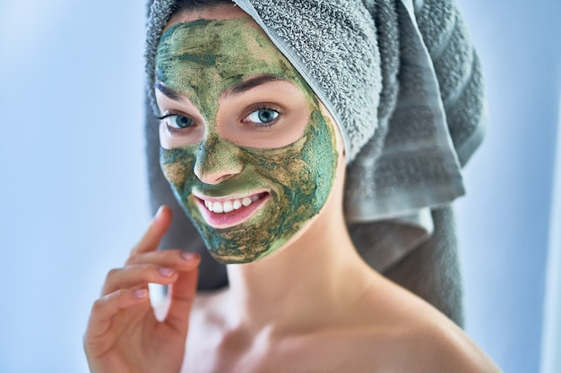 Portrait of young happy healthy female in bath towel with face clay mask after shower during spa day at home. face skin care