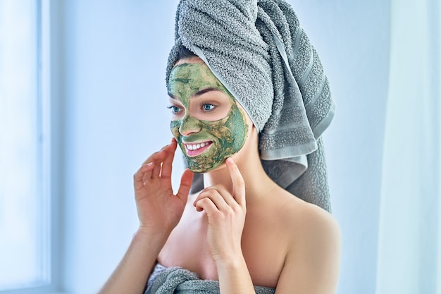 Portrait of young happy healthy woman in bath towel with green face clay mask after shower during spa day at home. face skin care