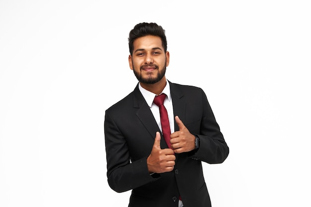 Portrait of young happy indian business man on white isolated background looking to the camera.