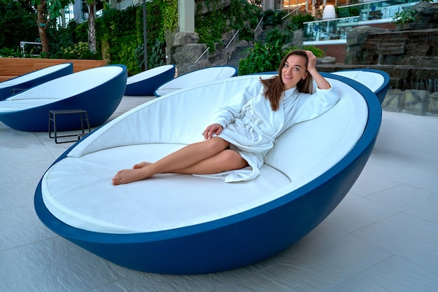 Портрет молодой счастливой радостной красивой женщины брюнет в белом халате, наслаждаясь расслабляющим временем и чувствуя себя хорошо на оздоровительном спа-курорте. легкий образ жизни