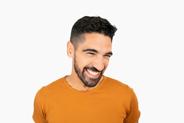 Portrait of young happy man smiling against white background in studio.