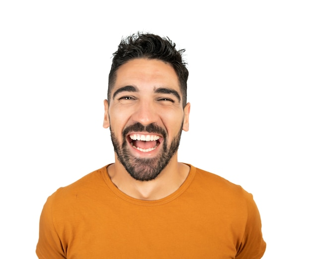 Portrait of young happy man smiling against white background in studio
