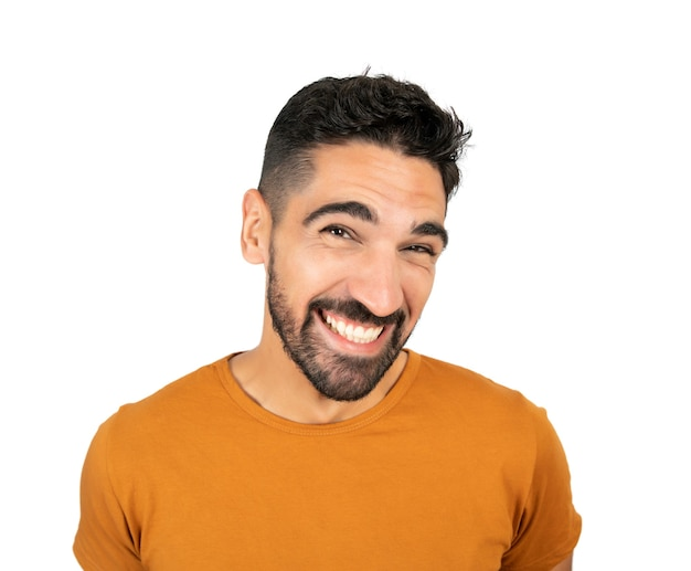 Portrait of young happy man smiling against white wall.