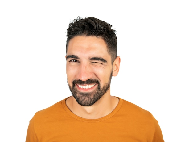 Portrait of young happy man smiling while winking an eye against white wall.