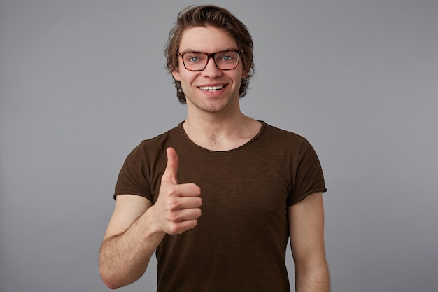 Portrait of young happy man with glasses, stands over gray background with cheerful expression, shows like gesture and broadly smiles.