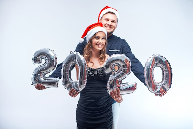 Portrait of young happy man and woman in red santa hats with 2020 metallic balloons.
