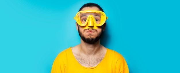 Portrait of young happy man in yellow, wearing diving mask and snorkel on blue background.