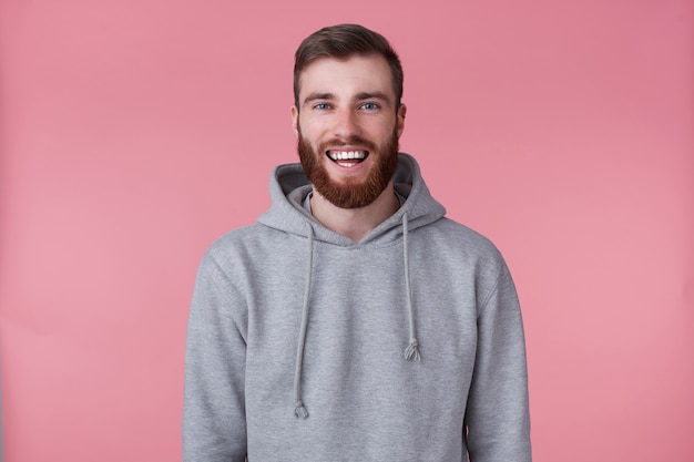 Portrait of young happy red bearded man in gray hoodie, looks happy and broadly smiles, stands.