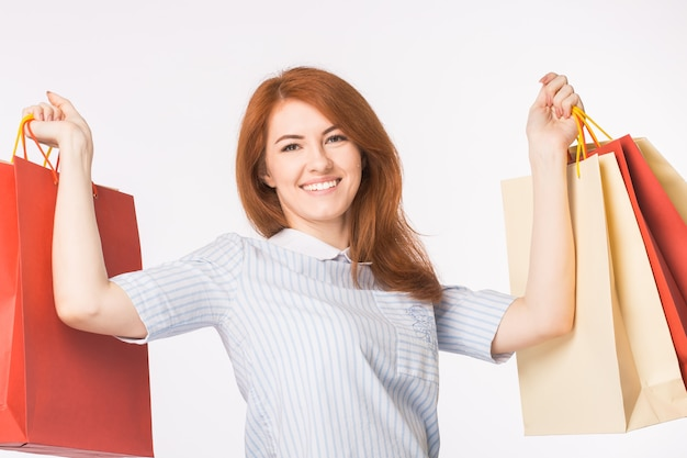 Portrait of young happy red-haired woman with shopping bags on white background