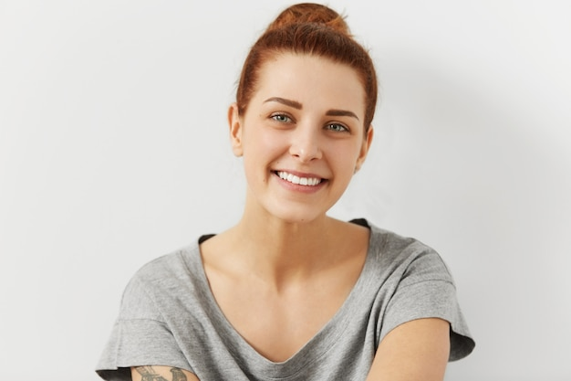 Portrait of young happy red haired woman with tattoo on her shoulder