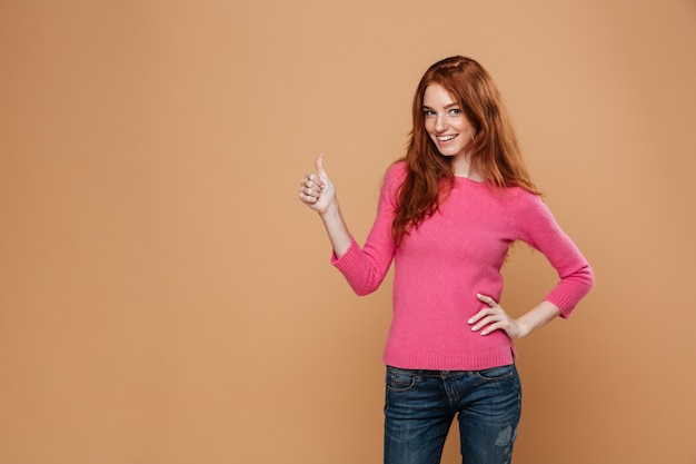 Portrait of a young happy redhead girl looking happy with thumbs up