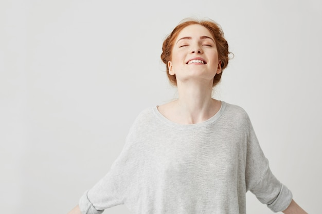 Portrait of young happy redhead girl smiling with closed eyes .