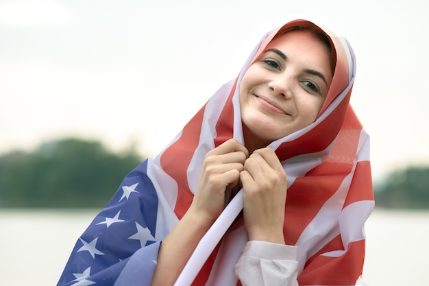 Portrait of young happy refugee woman with usa national flag on her head and shoulders. positive muslim girl celebrating united states independence day.