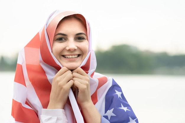 Portrait of young happy refugee woman with usa national flag on her head and shoulders.