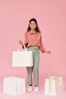 Portrait of young happy shopaholic standing among shopping bags and smiling against the pink background