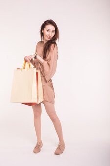 Portrait of young happy smiling asian woman with shopping bags on white wall