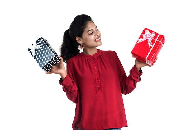 Portrait of young happy smiling girl holding and posing with gift boxes on a white background.