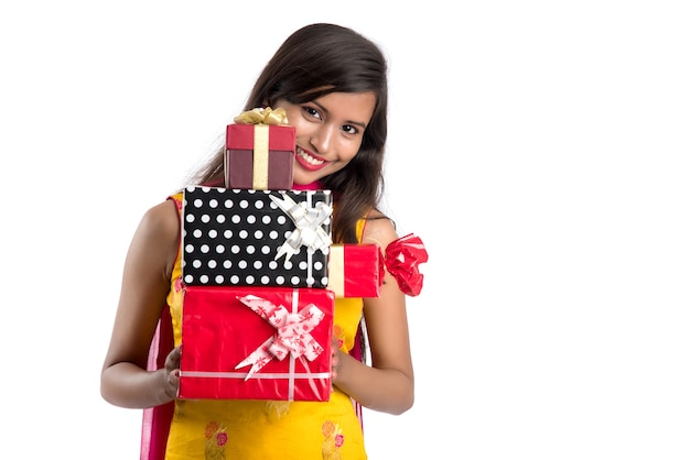 Portrait of young happy smiling indian girl holding gift boxes on a white wall.