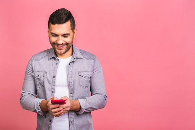 Portrait of young happy smiling man in casual typing sms. using phone.