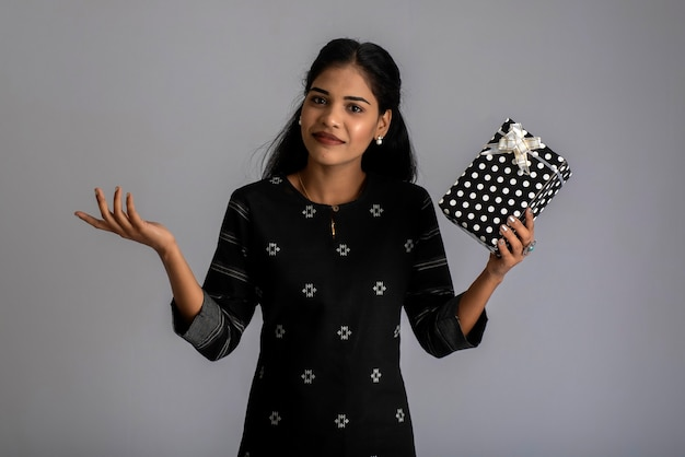Portrait of young happy smiling woman girl holding gift box on a grey background.