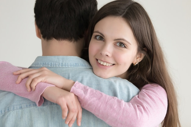 Portrait of young happy smiling woman hugging man with love