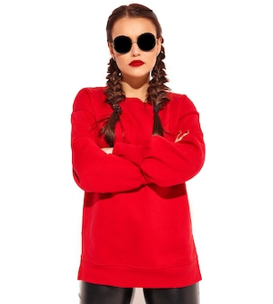 Portrait of young happy smiling woman model with bright makeup and colorful lips with two pigtails and sunglasses in summer red clothes isolated. сrossed arms