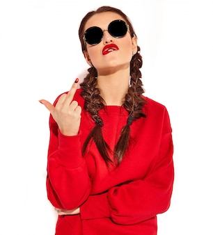Portrait of young happy smiling woman model with bright makeup and colorful lips with two pigtails and sunglasses in summer red clothes isolated. showing fuck off sign